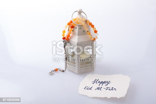istock the word EID EL FITR   on torn paper beside lantern and prying beads 974859056