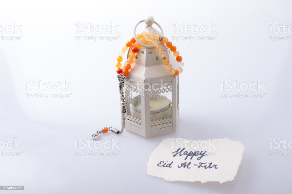 the word EID EL FITR   on torn paper beside lantern and prying beads stock photo