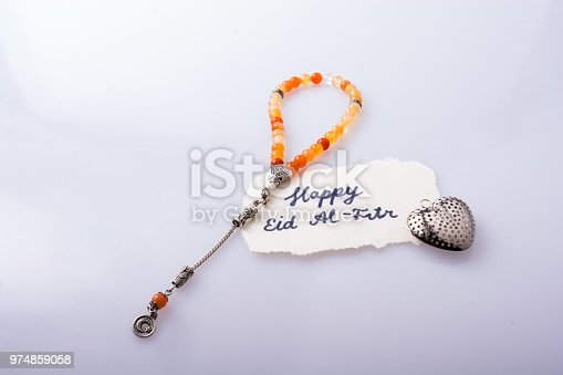 istock the word EID EL FITR   on torn paper beside prying beads 974859058