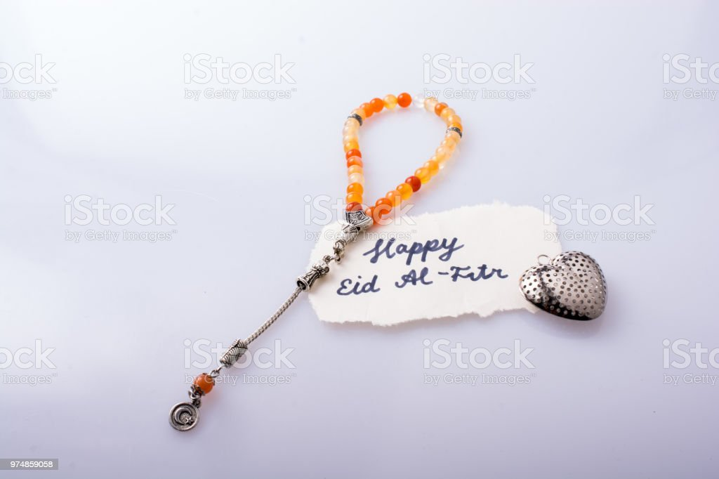 the word EID EL FITR   on torn paper beside prying beads stock photo