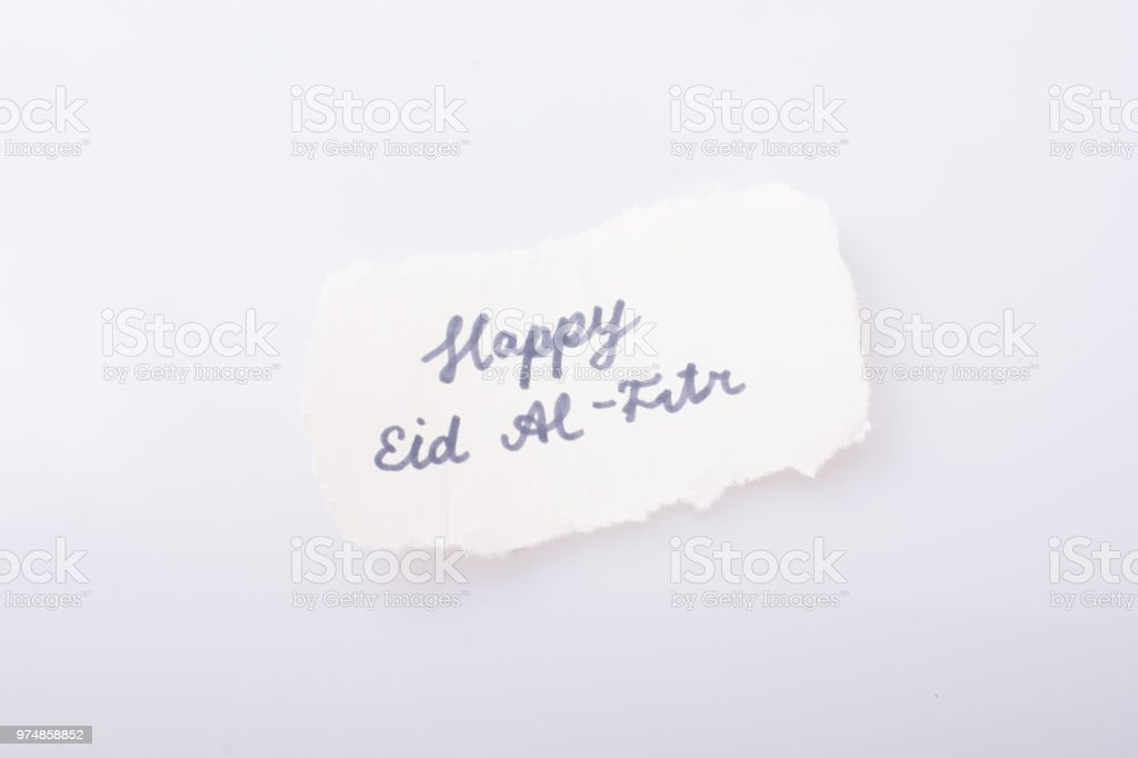 the word EID EL FITR  written on torn paper stock photo