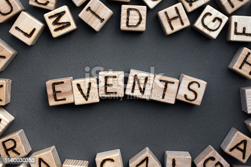 the word events wooden cubes with burnt letters, celebration, gray background top view, scattered cubes around random letters