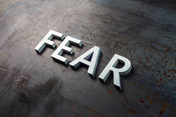the word fear laid with silver letters on raw rusted steel sheet surface in diagonal slanted composition stock photo