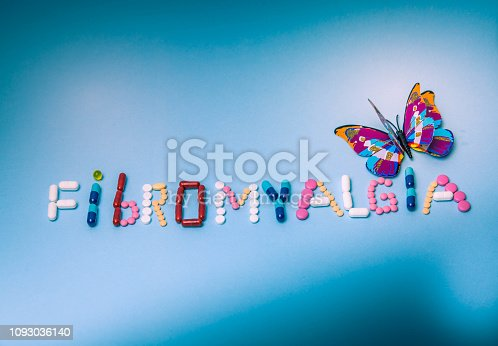 istock The word Fibromyalgia written by colorful medicines, pills, drugs, tablets, capsules, with purple butterfly on a blue background 1093036140