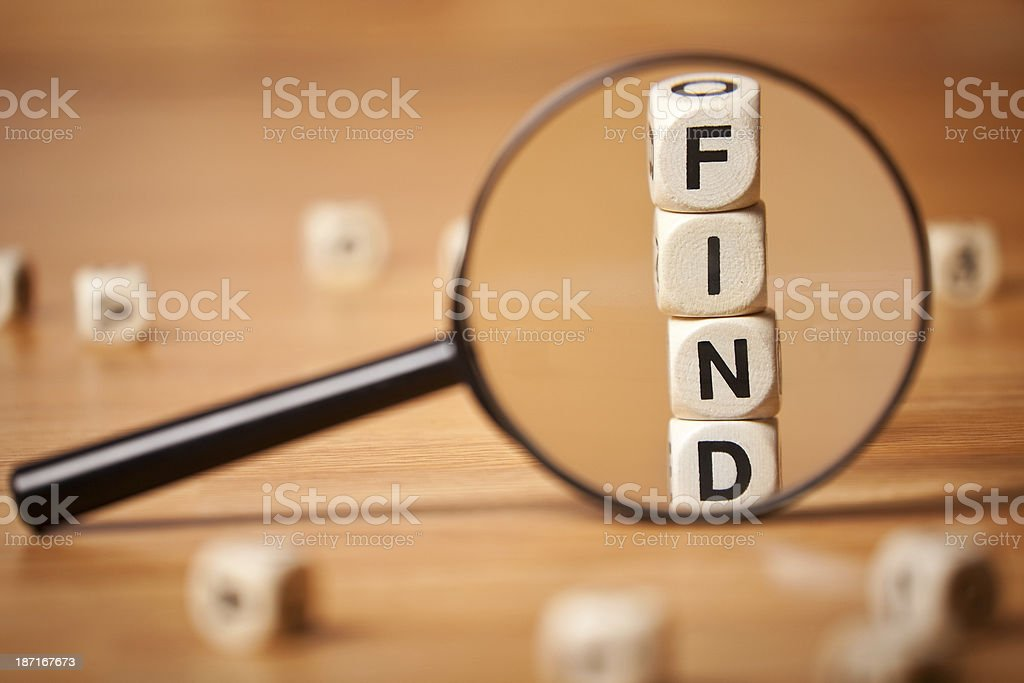 The Word FIND Spelled In Letter Cubes Through Magnifying Glass royalty-free stock photo