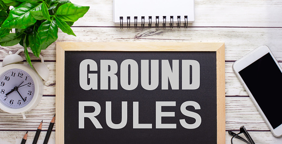 The word GROUND RULES written on a black background near pencils, a smartphone, a white notepad and a green plant in a pot