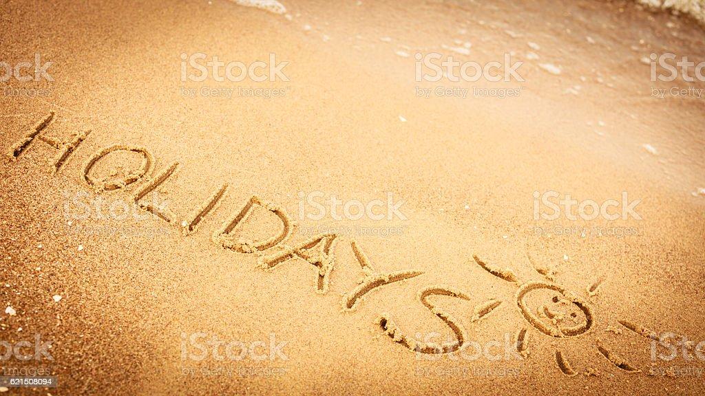Le mot vacances écrit dans le sable sur la plage  photo libre de droits