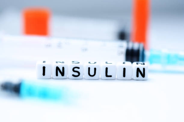The word insulin spelled with plastic letter beads next to a syringe stock photo