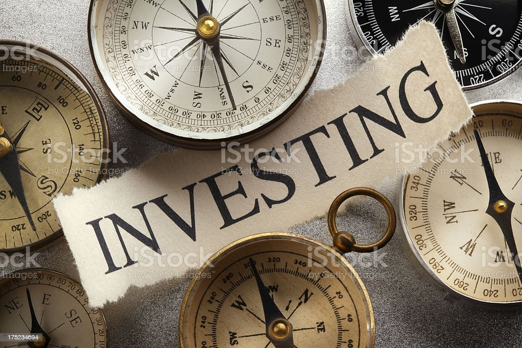 The word investing on grouping of compasses stock photo