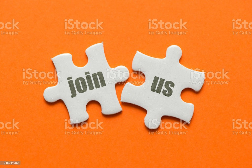 The word Join Us! on two matching puzzle on orange background stock photo