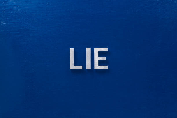 the word lies laid with silver metal letters on classic blue board in flat lay with central composition stock photo