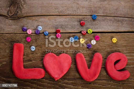 istock The word LOVE  and  colorfull buttons on wooden background 530742758