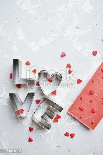 istock the word love is lined with metal letters and many small hearts on a gray background 1264346223
