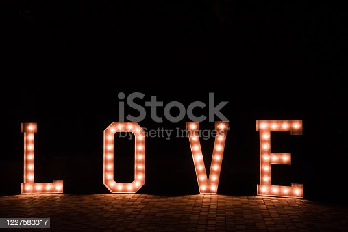 The word Love of bulbs on a black background. Festive illumination and romantic atmosphere