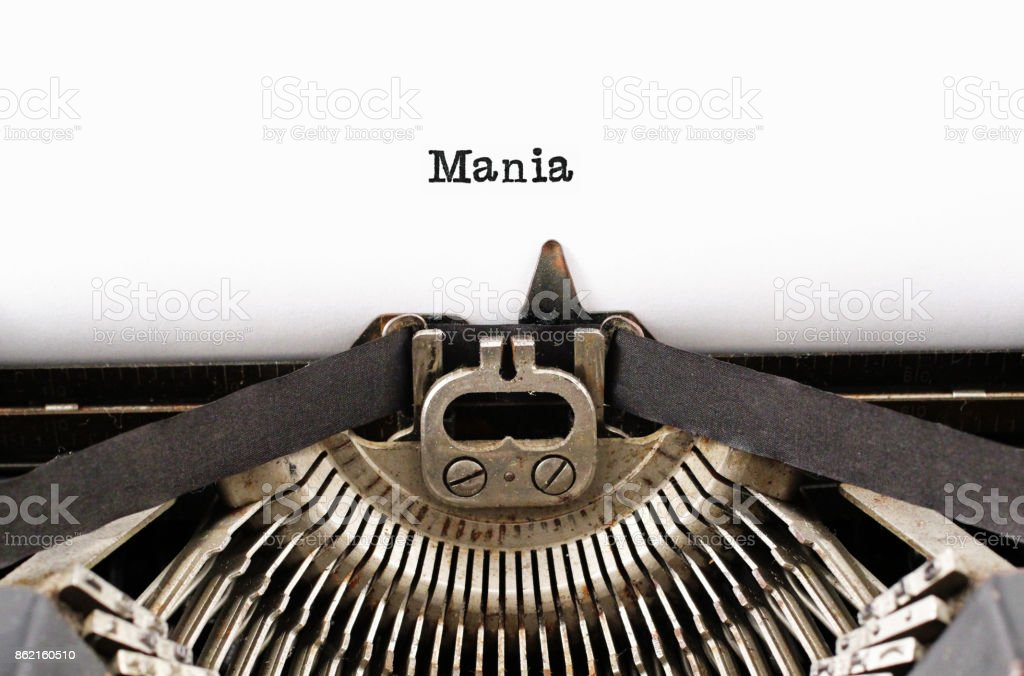 The word 'Mania' from a typewriter on white stock photo