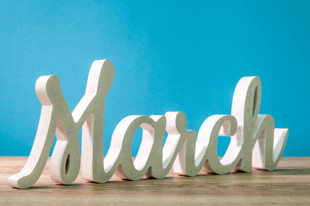 the word march carved of wood at blue background. spring beginning concept - marzo foto e immagini stock