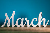 istock the word MARCH - wooden text at dark blue background. Spring concept 655969048