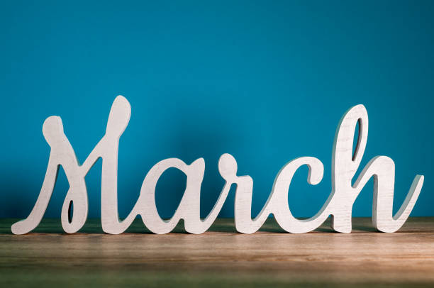 the word march - wooden text at dark blue background. spring concept - marzo foto e immagini stock