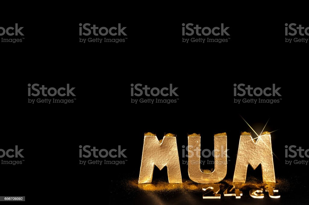 The word MUM in gold bullion letters. Black background copy space. stock photo