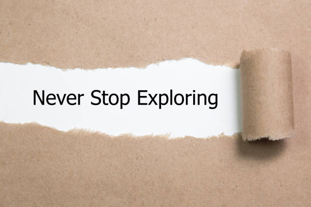 The word never stop exploring appearing behind torn paper. The word never stop exploring appearing behind torn paper. descry stock pictures, royalty-free photos & images