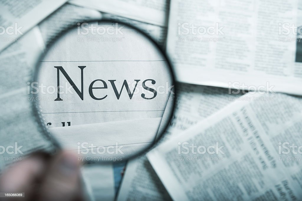 The word News under a magnifying glass among stacks of paper stock photo