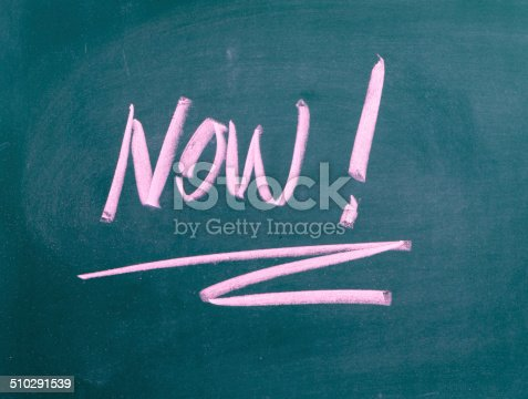 The word Now! on a used blackboard. A time management concept image for taking action or seizing the day instead of delay or procrastination.