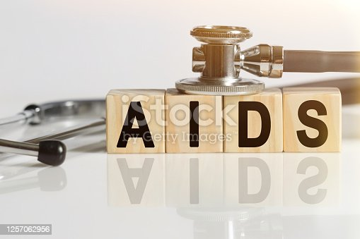 istock AIDS the word on wooden cubes, cubes stand on a reflective white surface, on cubes - a stethoscope. 1257062956