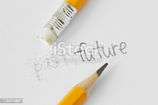 The word past erased with a rubber and the word future written with a pencil on white paper - Concept of time, clearing the past and building a future
