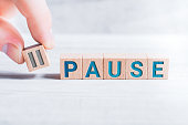 The Word Pause Formed By Wooden Blocks And Arranged By Male Fingers On A White Table