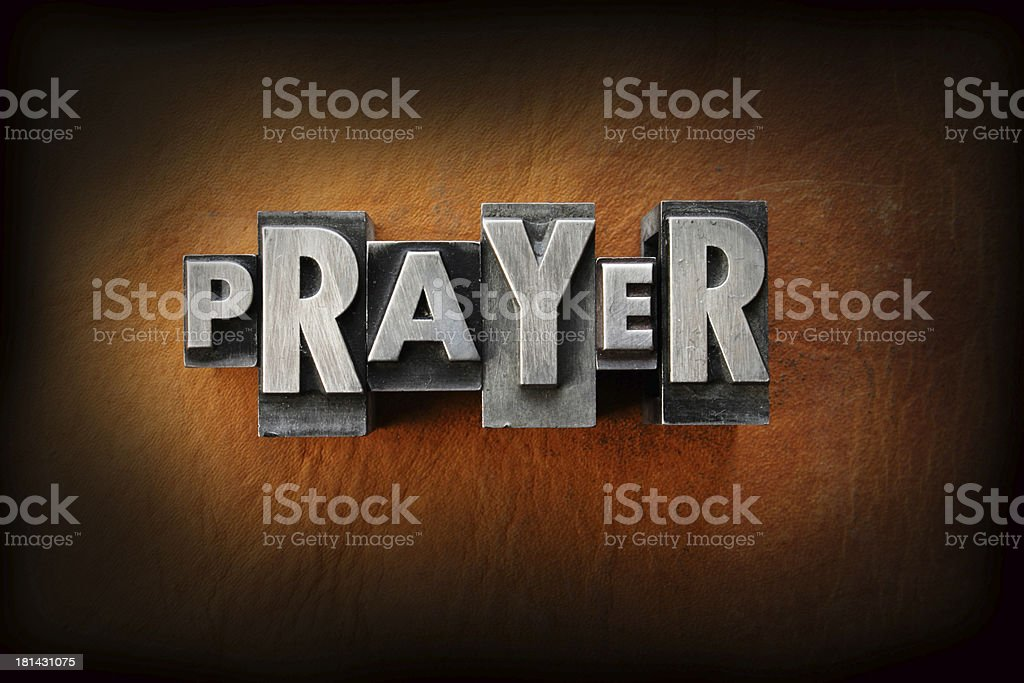 The word prayer in gray letters on a brown wall stock photo