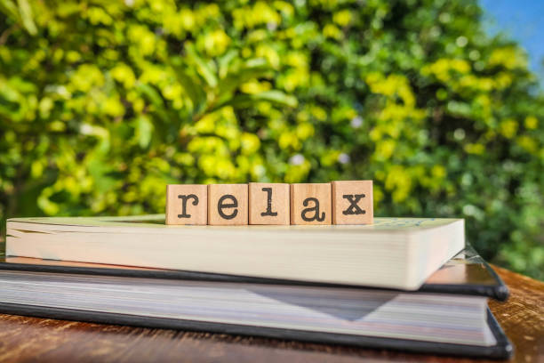The word RELAX, letters cubes on books with green trees, nature background. stock photo