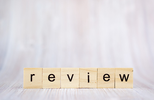 1163501702 istock photo The word review on wooden cube blocks on white wooden table. Review concept 1171009630