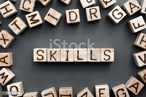 the word skills wooden cubes with burnt letters, skill acquisition, gray background top view, scattered cubes around random letters