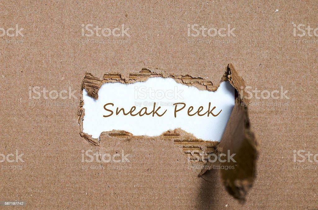 The word sneak peek appearing behind torn paper. stock photo