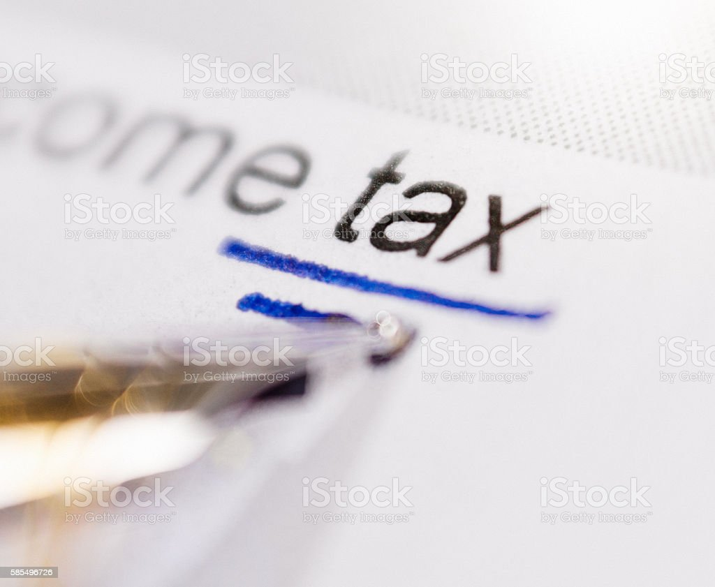 The word 'tax' being underlined on a document stock photo