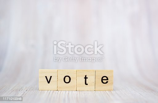 The word Vote on wooden cube block on wood table.