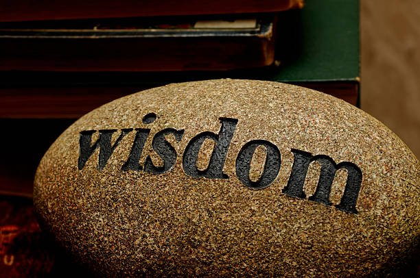 The word wisdom etched into a stone stock photo