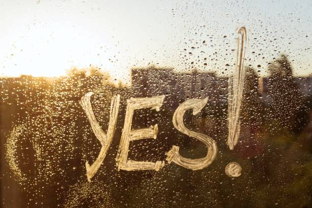 The word yes on the window with water drops on sunny background, yes written with white toothpaste The word yes on the window with water drops on sunny background, yes written with white toothpaste. yes single word stock pictures, royalty-free photos & images