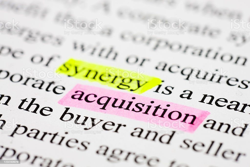 The words acquisition and synergy highlighted in business text  Achievement Stock Photo