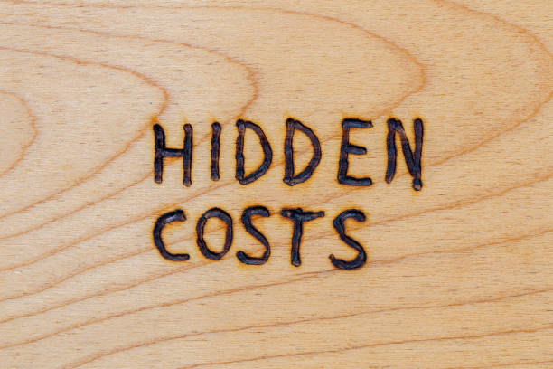 the words hidden costs handwritten with woodburner on flat wood surface - directly above flat lay composition view stock photo