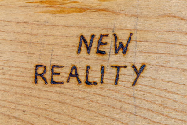 the words new reality handwritten with woodburner tool on flat wood surface stock photo