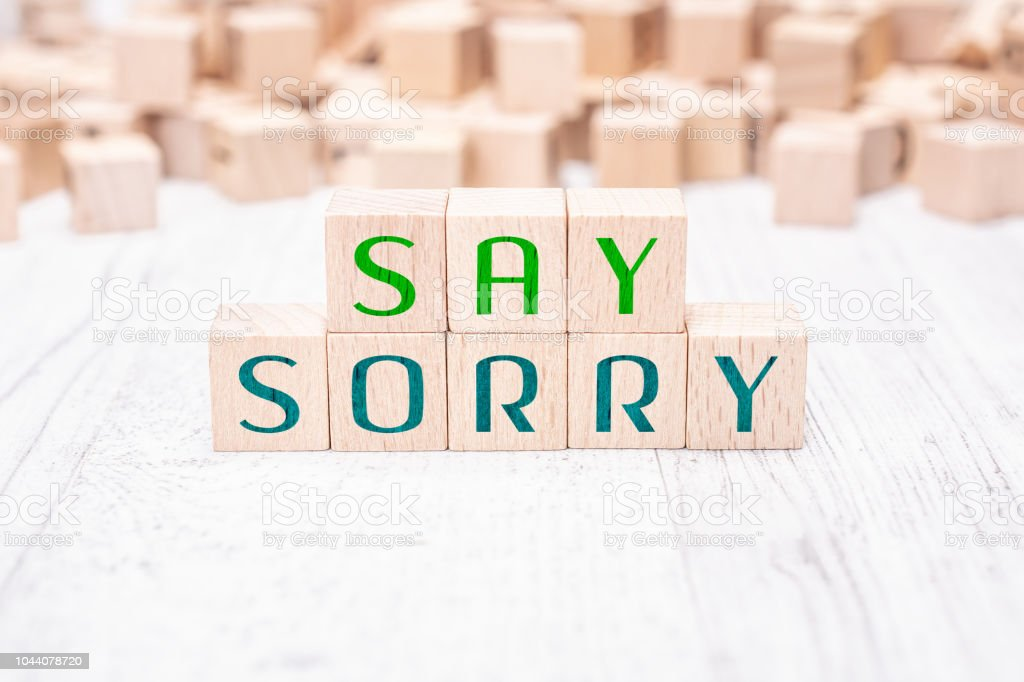 The Words Say Sorry Formed By Wooden Blocks On White Table