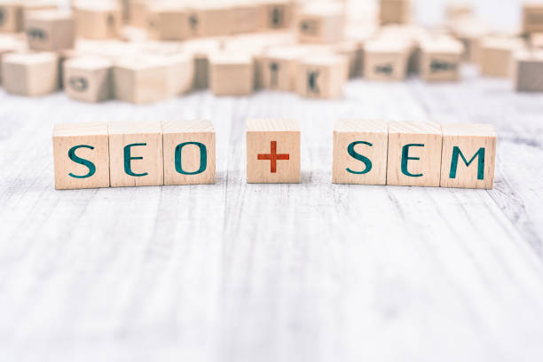 The Words SEO And SEM Formed By Wooden Blocks On A White Table stock photo