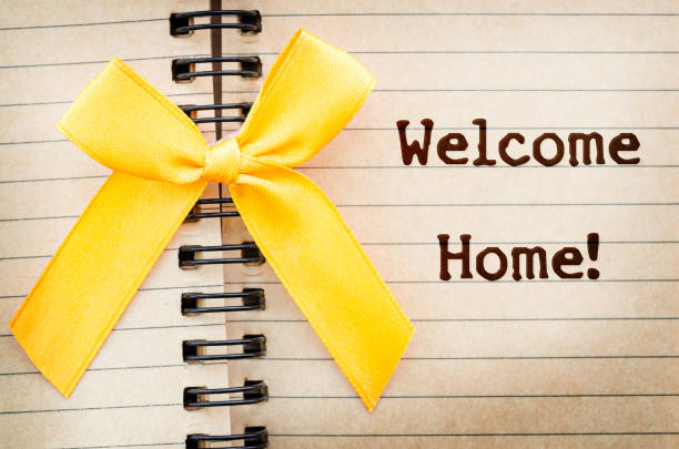 The words Welcome Home written on a old brown diary paper The words Welcome Home written on a old brown diary paper next to a yellow ribbon,in reference to military returning from overseas duty. war effort stock pictures, royalty-free photos & images