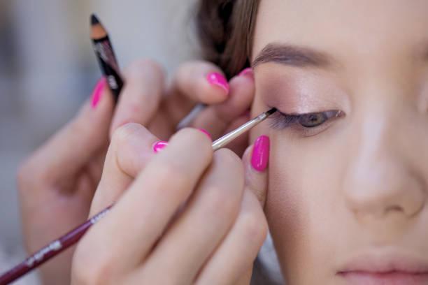 El trabajo de un maquillador profesional. Estilista maquilladora maquillando y peinando en un salón de belleza. - foto de stock