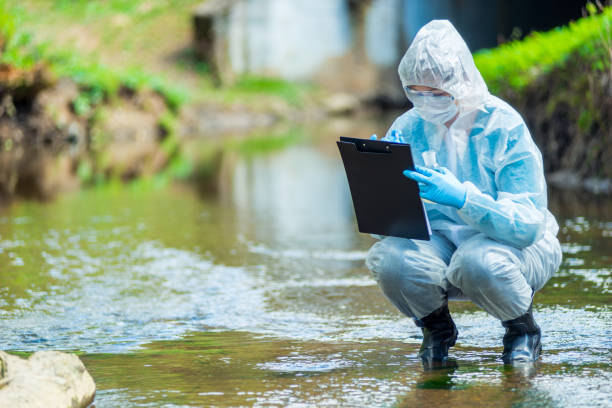 the work of a scientist ecologist, a portrait of an employee who conducts a study of water in a creek the work of a scientist ecologist, a portrait of an employee who conducts a study of water in a creek sewage treatment plant stock pictures, royalty-free photos & images