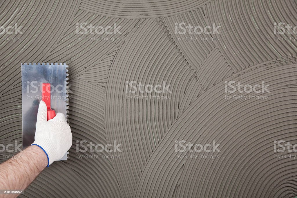 the worker applies glue for a tile on a wall stock photo