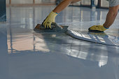 istock The worker applies gray epoxy resin to the new floor 1295831125