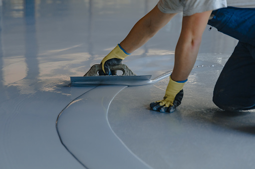 The worker applies gray epoxy resin to the new floor