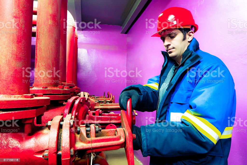 The worker closes a latch of the industrial pipeline. stock photo